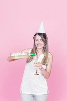 Gelukkige jonge vrouw vieren met wijn op roze achtergrond