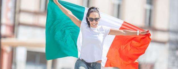 Gelukkige jonge vrouw viert de overwinning van italië op een straat met een vlag in haar handen.