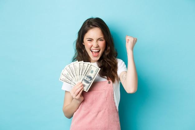 Gelukkige jonge vrouw ziet er opgewonden uit, schreeuwt van tevredenheid en triomf, wint geld, houdt dollarbiljetten vast en maakt vuistpomp, staande over blauwe achtergrond
