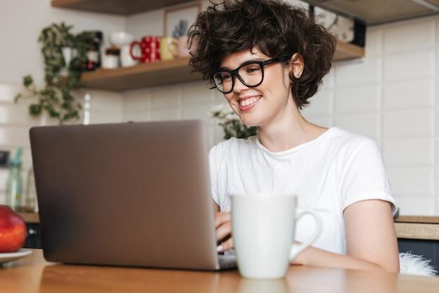 Gelukkige jonge vrouw zit binnenshuis in de keuken met laptopcomputer