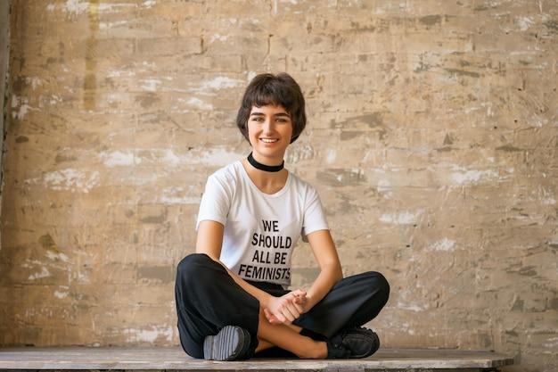 Gelukkige jonge vrouw zit in een wit t-shirt met de woorden dat we allemaal feministen moeten zijn, concept