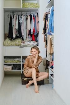 Gelukkige jonge vrouw zit op oude koffer in kleedkamer