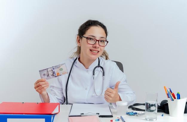 Gelukkige jonge vrouwelijke arts die medische mantel en een stethoscoop en een bril draagt die aan bureau met medische hulpmiddelen zit die geld op zoek toont duim omhoog geïsoleerd