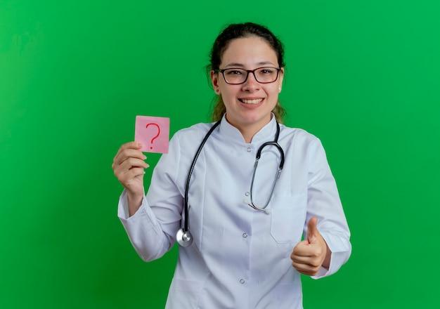 Gelukkige jonge vrouwelijke arts die medische mantel en stethoscoop en glazen draagt die vraagnota houdt die duim toont die omhoog op groene muur met exemplaarruimte wordt geïsoleerd