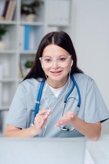 Gelukkige jonge vrouwelijke clinicus in uniform en bril die naar online patiënt luistert en medische aanbevelingen geeft terwijl hij aan het bureau zit