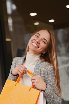 Gelukkige jonge vrouwelijke klant in stijlvolle outfit glimlachend met tevredenheid terwijl vrije tijd doorbrengen in winkelcentrum en genieten van aankopen