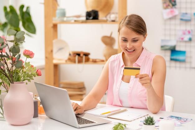 Gelukkige jonge vrouwelijke online shopper met plastic kaart die zijn nummer invoert tijdens het maken van bestelling in het net