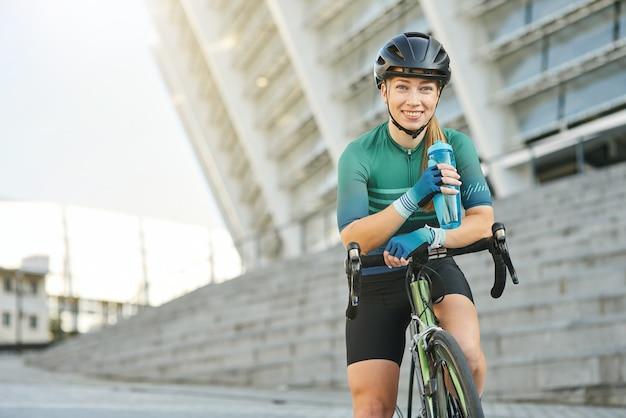 Gelukkige jonge vrouwelijke professionele vrouwelijke wielrenner die naar de camera glimlacht terwijl ze een waterfles vasthoudt