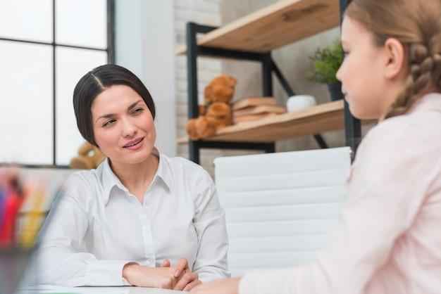 Gelukkige jonge vrouwelijke psycholoog die meisje in het bureau bekijkt