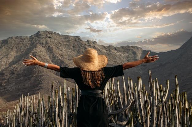 Gelukkige jonge vrouwelijke reiziger in jurk met strohoed die geniet van de zomerreis op het eiland fuerteventura