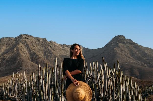 Gelukkige jonge vrouwelijke reiziger in jurk met strohoed in de hand die geniet van de zomerreis op het eiland fuerteventura terwijl hij in de buurt van groene cactusplanten staat tegen rotsachtige vulkanische heuvels en blauwe lucht