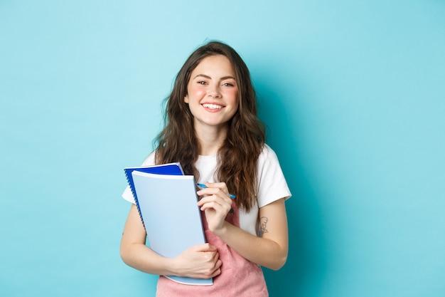 Gelukkige jonge vrouwelijke student die notebooks van cursussen vasthoudt en naar de camera glimlacht, staande in lentekleding tegen een blauwe achtergrond.