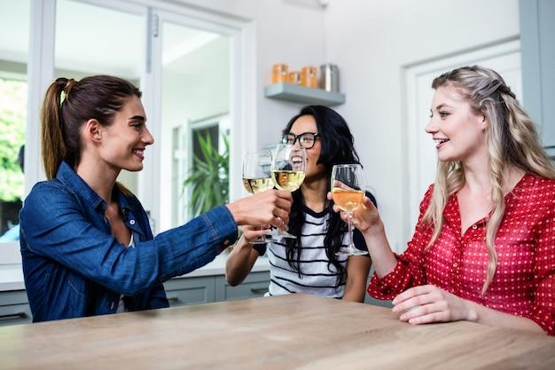 Gelukkige jonge vrouwelijke vrienden die wijnglas roosteren