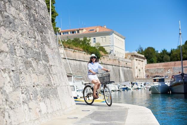 Gelukkige jonge vrouwen berijdende fiets op steenweg langs het overzees door hoge steenmuur op heldere zonnige de zomerdag. sightseeing, toerisme, sport en actieve levensstijl concept.