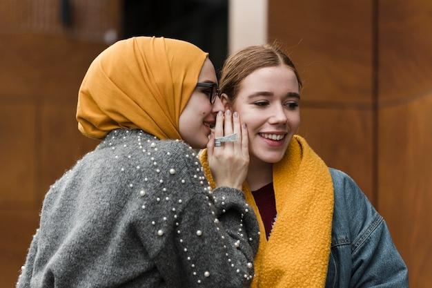 Gelukkige jonge vrouwen die aan elkaar fluisteren