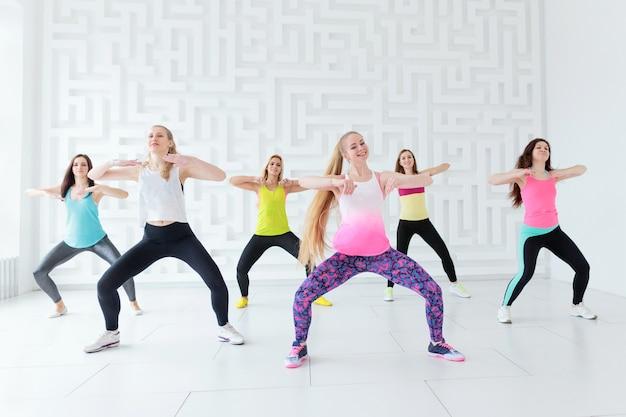 Gelukkige jonge vrouwen die een fitness-dansles hebben in de dansstudio