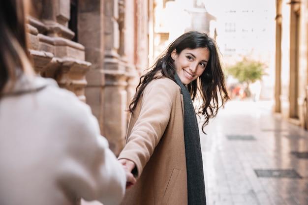 Gelukkige jonge vrouwen die handen op straat houden