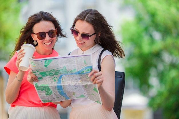 Gelukkige jonge vrouwen die met toeristische kaart op europese straat lopen.