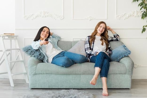 Gelukkige jonge vrouwen die op laag en op tv zitten zitten