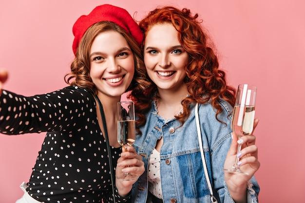 Gelukkige jonge vrouwen die selfie met champagne op roze achtergrond nemen. vooraanzicht van opgewonden meisjes met wijngassen.