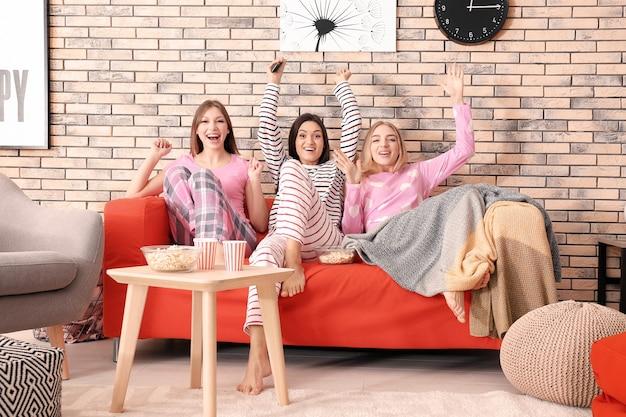 Gelukkige jonge vrouwen die thuis naar sport kijken