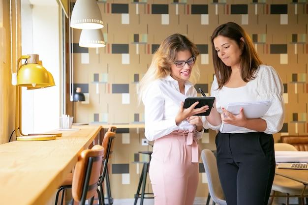 Gelukkige jonge vrouwen die via tablet naar designtrends zoeken en glimlachen