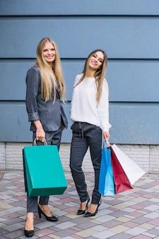 Gelukkige jonge vrouwen die zich voor muur bevinden die het winkelen zakken houden