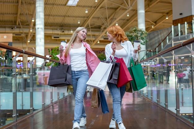 Gelukkige jonge vrouwen met boodschappentassen genieten van winkelen, meisjes hebben plezier met hun aankopen. consumentisme en levensstijl concept