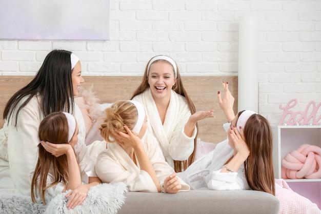 Gelukkige jonge vrouwen tijdens vrijgezellenfeest thuis