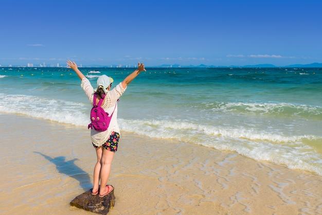 Gelukkige jonge vrouwen uitspreidende hand op het strand voor het ontspannen.
