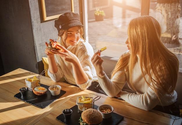 Gelukkige jonge vrouwen zitten aan tafel en kijken elkaar aan
