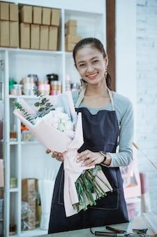 Gelukkige jonge vrouwenbloemist die in bloemenwinkel werken die flanellenbloem bekijken die de camera bekijken