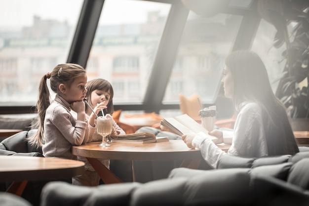 Gelukkige jonge vrouwenmoeder met kinderen die bij dinerlijst zitten en in restaurant spreken