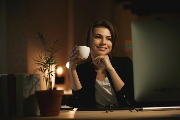 Gelukkige jonge vrouwenontwerper bij nacht die computer met behulp van