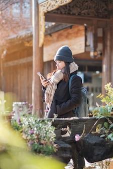 Gelukkige jonge vrouwenreiziger die mobiele telefoon of plankie fotografie met behulp van