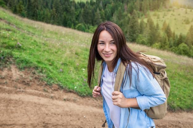 Gelukkige jonge vrouwentoerist loopt met rugzak in de hooglanden. actief levensstijlconcept
