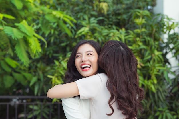Gelukkige jonge vrouwenvrienden die goed gekleed glimlachen terwijl ze samen knuffelen
