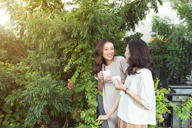 Gelukkige jonge vrouwenvrienden die goed gekleed glimlachen terwijl ze samen staan