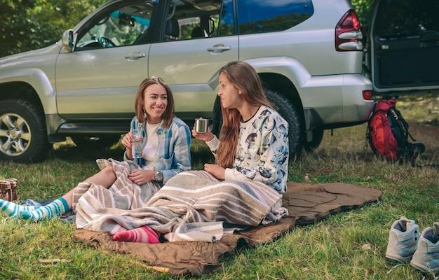 Gelukkige jonge vrouwenvrienden die praten en rusten onder een deken op de camping in het bos