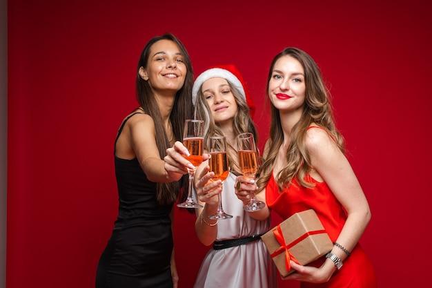 Gelukkige jonge vrouwenvrienden met gift en champagne die vakantie samen vieren op partij op rode muur, exemplaarruimte