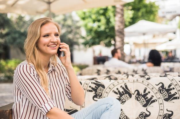 Gelukkige jonge vrouwenzitting bij openluchtrestaurant die op mobiele telefoon spreken
