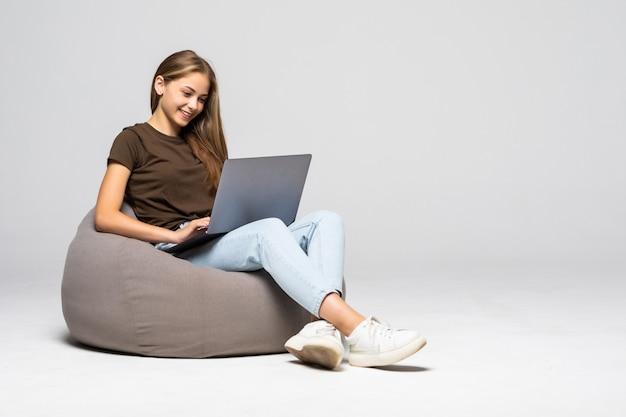 Gelukkige jonge vrouwenzitting op de vloer die laptop op grijze muur met behulp van
