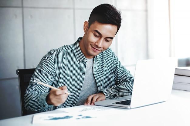 Gelukkige jonge zakenman die aan computerlaptop in bureau werkt. glimlachen en schrijven op papier
