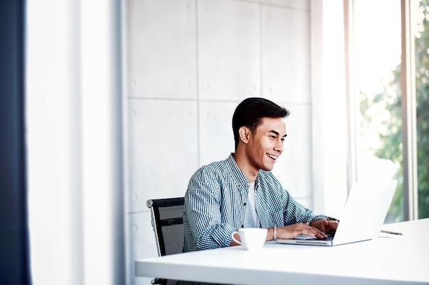 Gelukkige jonge zakenman die aan computerlaptop in bureau werkt.