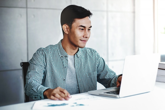 Gelukkige jonge zakenman die aan computerlaptop in bureau werkt