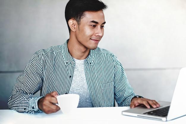 Gelukkige jonge zakenman die aan computerlaptop werkt in bureau. glimlachend en kijkend naar de computer