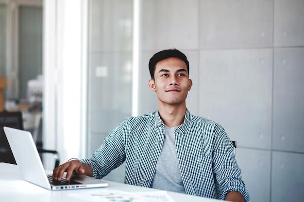 Gelukkige jonge zakenman die aan computerlaptop werkt in bureau. glimlachend en wegkijken