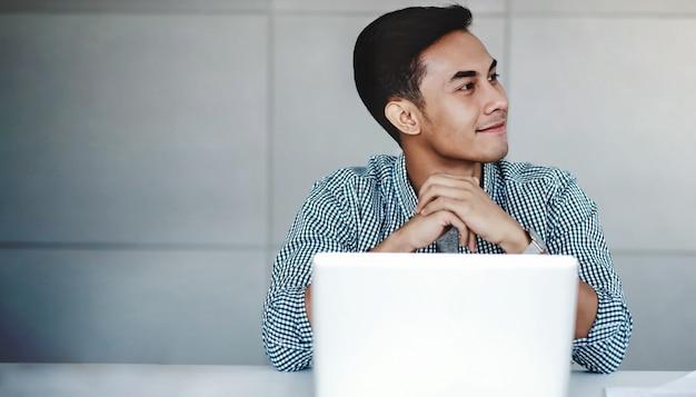 Gelukkige jonge zakenman die aan computerlaptop werkt in bureau