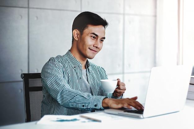 Gelukkige jonge zakenman die aan computerlaptop werkt terwijl het drinken van koffie in bureau