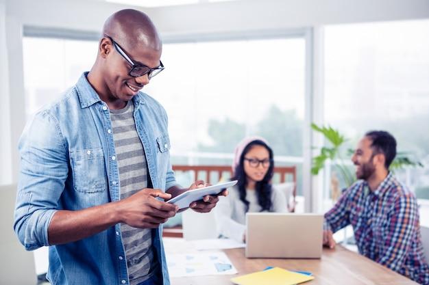 Gelukkige jonge zakenman die digitale tablet gebruiken terwijl status op kantoor